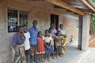 Elines (left) smiles happily along with some of her grandchildren in front of the family's new home.