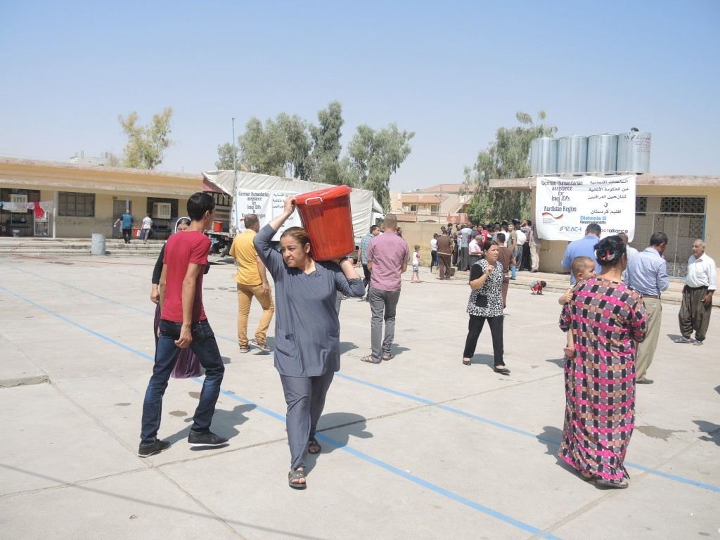 Iraqi refugees leave a school compound with relief goods in August 2014. Relief packages include water, tea, sugar, salt, flour and lentils, hygiene goods, mattresses, pots and kettles.