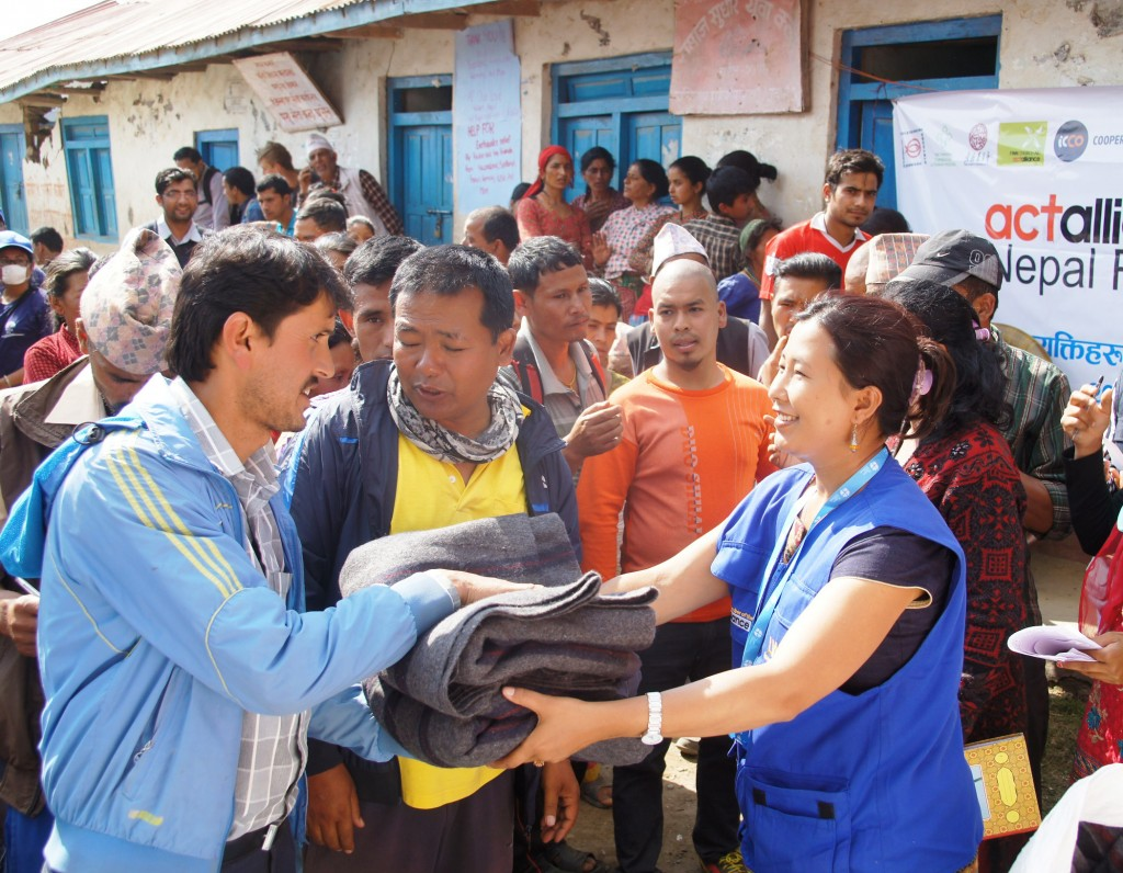 LWF Nepal project coordinator Nibha Shresta hands out blankets to earthquake survivors in Ghusel Credit: ACT Alliance/LWF, Cornelia Kästner