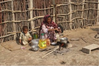Mrs. Dino makes food outside her home in Sajawal