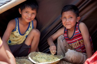 Young boys enjoy a meal under temporary shelter.