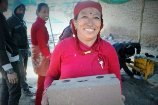 A woman carries an unfired brick in the community of Sanogoan. Photo: LWF/Lucia de Vries