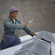 A man nails on tin roofing provided by the ACT Alliance as he puts the finishing touches on a transitional shelter in the Tamang village of Goljung, in the Rasuwa District of Nepal near the country's border with Tibet. In the aftermath of the April 2015 earthquake that ravaged Nepal, the Lutheran World Federation, a member of the ACT Alliance, helped people in this village with a variety of services, including blankets, shelter and livelihood assistance.