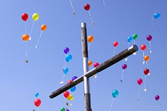 Cross with balloons against sky
