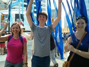 Pamela McCarroll, Ben McCaroll-Butler and Carragh Erhardt walk with KAIROS members in the March for Jobs, Climate and Justice that took place in Toronto, Sunday, July 5. The sign bearing blue streams reads,