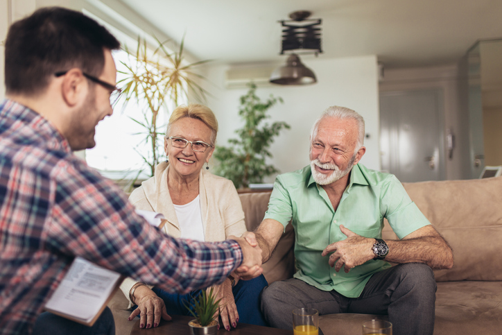 Aged couple consulting with young businessman